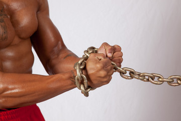 muscular black man with hands chained