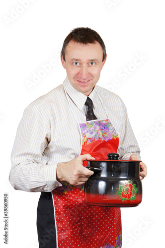 Man in a kitchen apron holds a pan