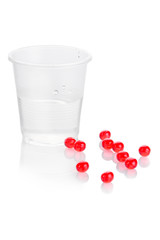 Pharmacy. Red vitamin pills and plastic cup of water on white