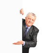A smiling mature businessman holding a white panel and gesturing