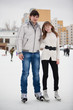 Couple on ice skate rink outdoors.
