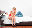 Disappointed blond female sitting on a bed while her boyfriend i