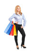 Full length portrait of a smiling woman posing with shopping bag