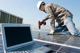 worker with scredriver and laptop on a photovoltaic plant