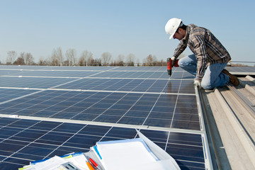 Man with scredriver on a photovoltaic plant