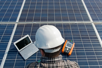 Man testing a photovoltaic plant with laptop
