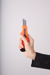 woman hand detail holding an orange cutter