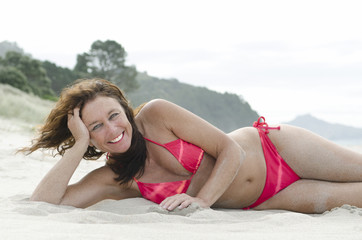 Mature woman sunbathing on beach