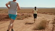 Young couple jogging on desert track, slow motion