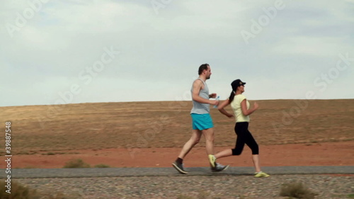 Young couple jogging, exercising and drinking water