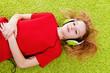 Leinwanddruck Bild - girl is listening to music with headphones on green carpet