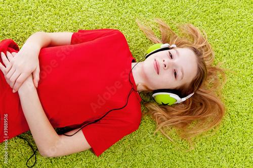 Leinwanddruck Bild girl is listening to music with headphones on green carpet