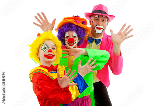 Three people dressed up as colorful funny clowns