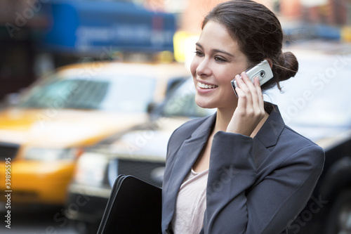 Young Woman Talking on Cell Phone by Yellow Taxi