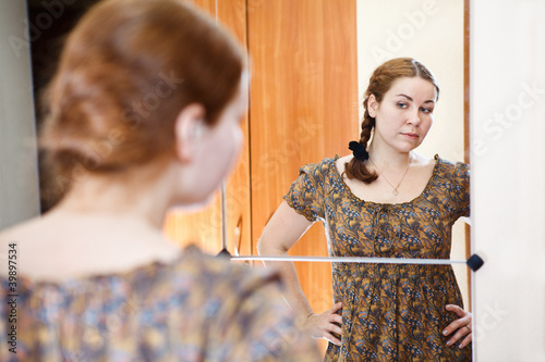 Young female in dress standing against mirror, looks at herself