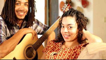 Mixed race couple sitting with guitar