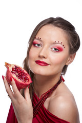 Portrait of young beautiful woman with pomegranates in her hands