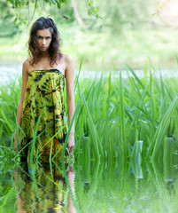 A young brunette in a green dress on a tropical background