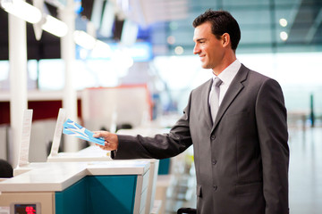 handsome businessman handing over air ticket at check in