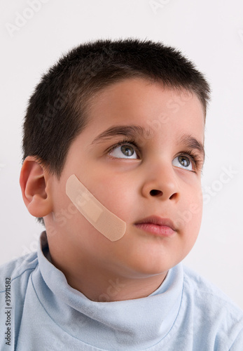 dhesive bandage on face of a child
