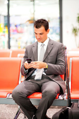 young businessman sending text messages at airport
