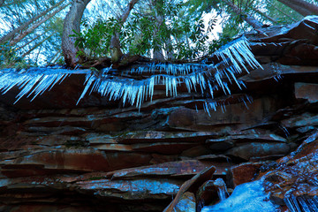 Icicles, rocks and hemlock pines perspective