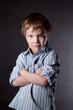 Serious boy on  black background.