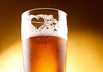 Glass of beer with the heart represented with froth close up ove