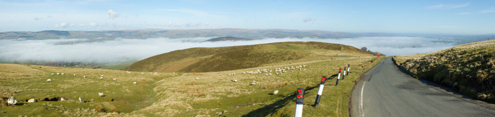 Panorama narrow road Welsh hills morning mist.
