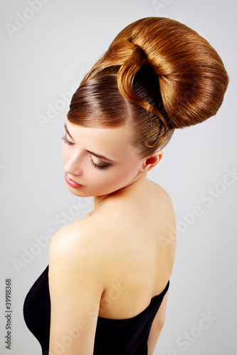 Beautiful girl with retro hairstyle on gray