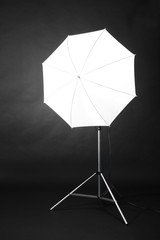 Studio flash with umbrella on grey background