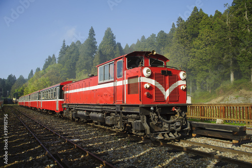 Red train under blue sky on railway forest in Alishan National S