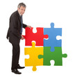 Senior businessman assembling a jigsaw puzzle
