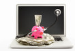 Piggy bank with stethoscope on laptop