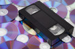 CD vs VHS. VHS cassette lay on the many CD disks