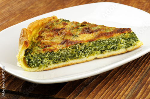 Slice of spinach tart with parmesan - wooden background