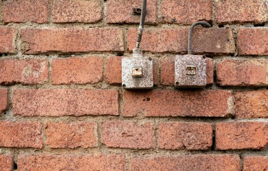 vintage industrial light switches on old weathered brick wall
