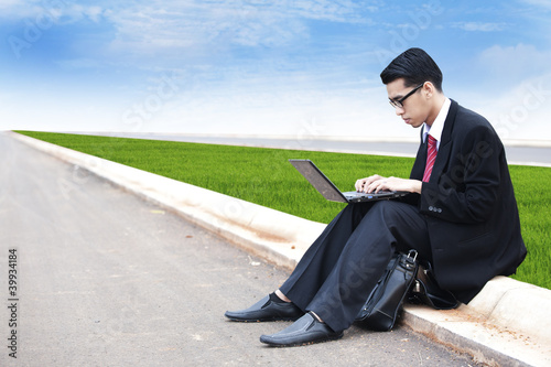 Businessman working with laptop outdoor