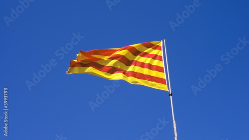 Catalonia flag waving in the breeze against blue sky