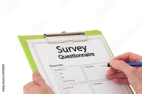 Hand with Pen Completing Market Research Survey Questionnaire