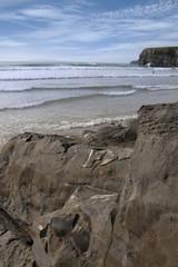 surfers near ballybunion cliffs and rocks