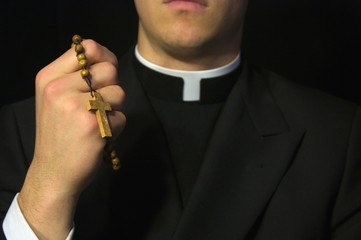 Young Priest praying with rosery in his hands