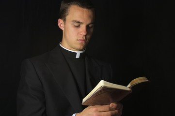 Young Priest in black reading prayer book