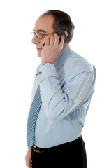 Side view of a senior manager attending phone call