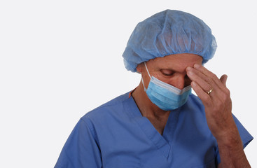 Surgeon with scrubs, mask, with hand on forehead