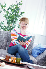 beautiful woman reading a book on the couch