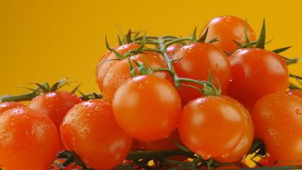 Cherry tomatoes rotating on orange background. Seamless loop.