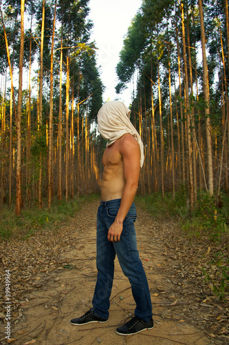 young man wondering in the woods head covered with shirt