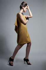 Fashion style - elegant brunette girl in trendy dress posing