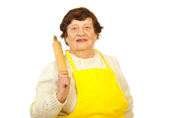 Smiling elderly holding rolling pin